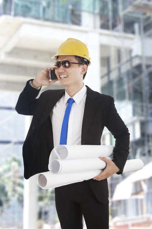 Happy asian businessman talking on the phone at construction site photo