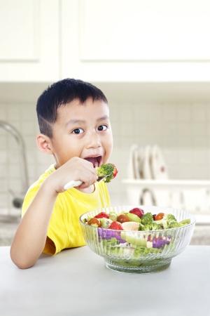 aceite de cocina: Niño asiático joven que come una porción grande de ensalada. un disparo en la cocina Foto de archivo