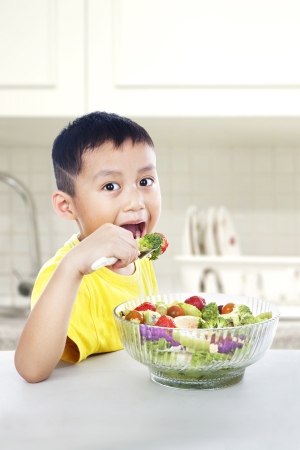 Young asian child eating a big portion of salad. shot in the kitchen room photo