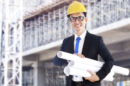 Smiling asian engineer with blueprints shot at workplace outdoor photo