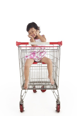 Adorable Asian girl with shopping trolley. Shot in studio isolated on white photo