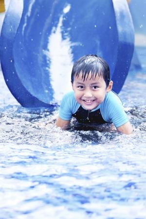 tobogan agua: Muchacho asi�tico feliz divirti�ndose con tobog�n de agua durante el verano
