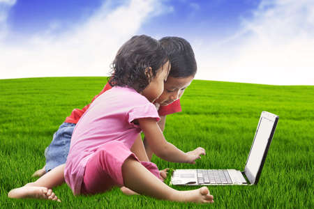 Young little sibling playing game on the laptop computer at meadow photo
