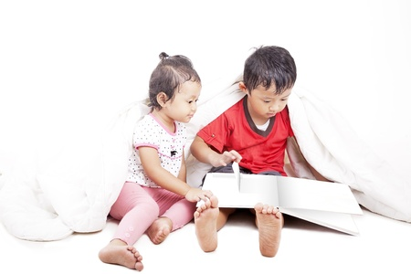 Young asian siblings reading book, shot in studio isolated on white photo