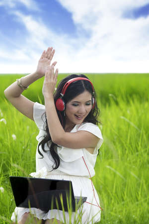 Young Asian woman listen to music enjoying summer outdoor Stock Photo - 14683088