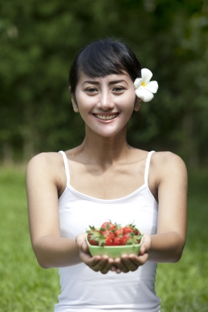 Beautiful Asian woman offering a bowl of strawberry Stock Photo - 14684469