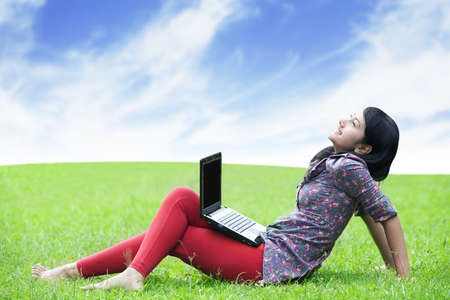 Young asian woman with laptop sitting on green grass