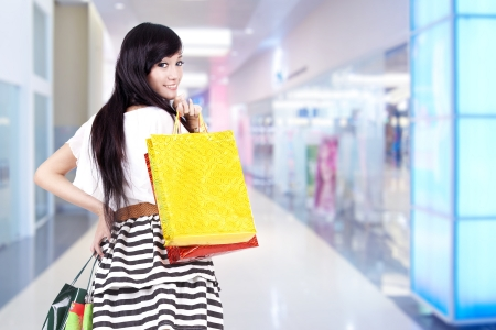 Beautiful Asian woman with shopping bags isolated over white photo