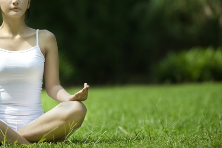Closeup photo of a beautiful asian woman in yoga position. Shot outdoor during summer photo