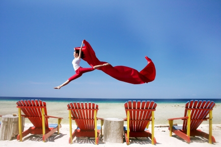 red chair: Young beautiful woman jumpiong at beautiful tropical beach