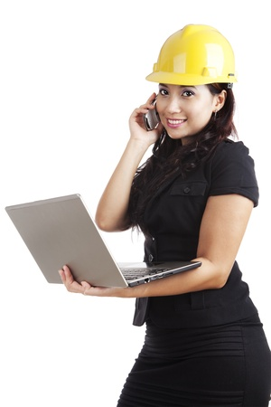 Beautiful Asian engineer holding laptop and a mobile phone photo