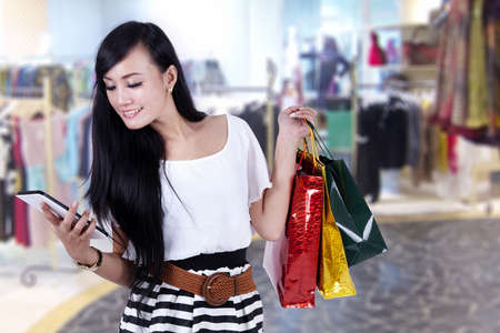 online shop: Beautiful asian woman looking at her computer tablet while carrying gift bags