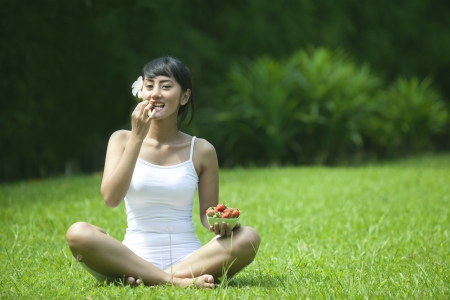 Healthy lifestlye photo concept with woman eating strawberry outdoor photo