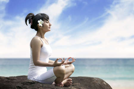 Beautiful asian woman meditating on the beach sitting over a rock photo