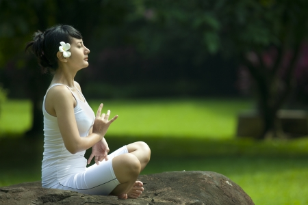 indian summer seasons: Pretty Asian woman in yoga position. Shot outdoor in a garden
