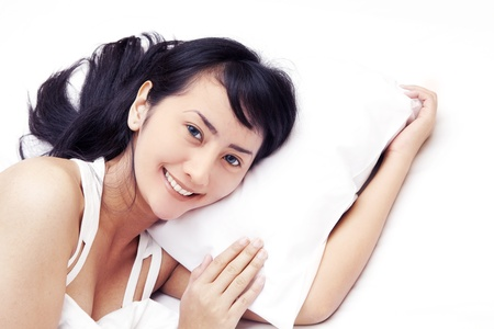Beautiful Asian woman smiling on bed shot in studio isolated on white with copy space photo