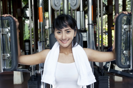 Pretty woman smiling while working out on a pet deck machine in a gym photo