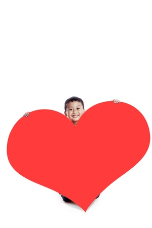 Smiling little boy with a huge heart cutout, shot in studio isolated on white background photo