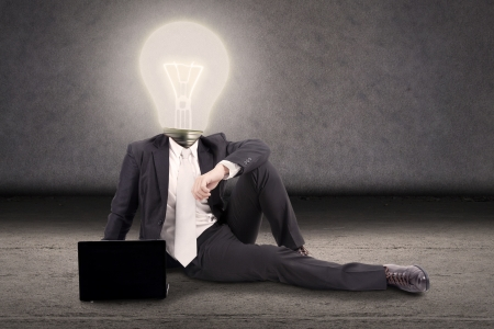 Bright idea concept: Businessman with head made of lightbulb sitting on the floor with laptop photo