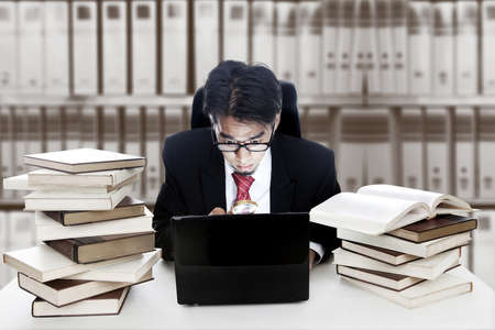 Job search concept - a businessman with laptop, magnify, and books photo