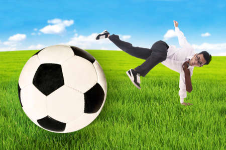 Business goal concept: Businessman kick a football to make a goal at field photo