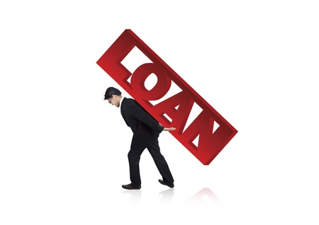 burdened: Anxious businessman carrying loan sign on his back. Can be used as business concept of heavy loan