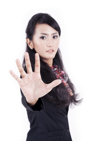 Young businesswoman showing hand gesture as a symbol of business restriction photo