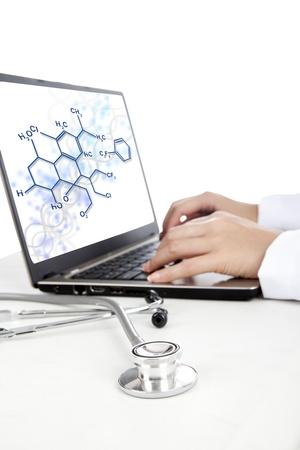 cientificos: Primer plano de un estetoscopio y las manos de los cient�ficos que trabajan en la computadora port�til para analizar la f�rmula qu�mica Foto de archivo