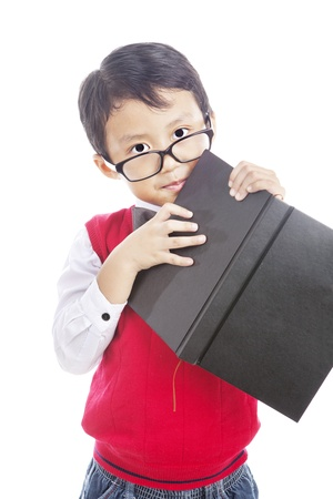 Portrait of male elementary school student holding book. shot in studio photo