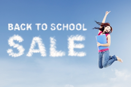 promotion girl: Text of back to school sale with female college student jumps on the side of text Stock Photo