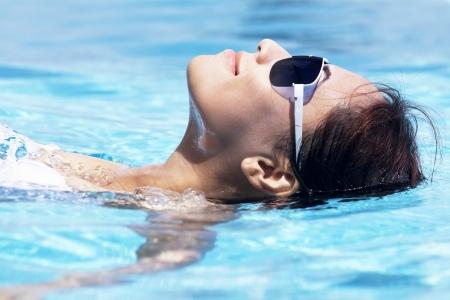 sensual: Jovem bonita que descansa na piscina no dia ensolarado mulher asi