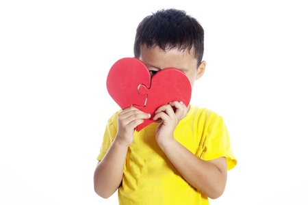 Cute boy peeking from behind heart shaped puzzle. shot in studio isolated on white photo