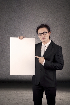 Young businessman pointing at an empty copyspace. shot in studio photo