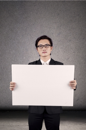 Young businessman showing blank white banner. shot in studio photo