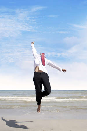 Happy businessman jumping at the beach to celebrate his success photo