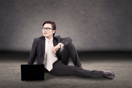 Young businessman with laptop sitting over grey background looked think something photo