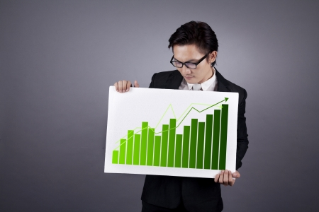 Successful businessman holding green graph of business growth. shot in studio photo