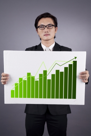 Successful businessman holding green graph of business growth. shot in studio Stock Photo - 14684442