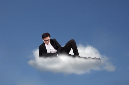 Cloud computing concept: Businessman working witt his laptop on a cloud photo