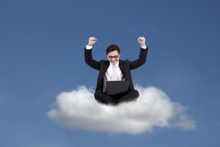 Cloud computing concept: Successful Asian businessman with laptop sitting on cloud photo