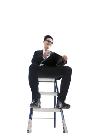 Young businessman checking list and sitting on ladder, isolated on white photo
