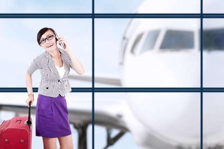 gente aeropuerto: Empresaria con maleta grande teniendo una conversación por teléfono, un disparo en el aeropuerto Foto de archivo