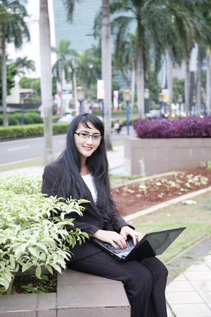 Portrait of beautiful businesswoman with laptop sitting at roadside of city photo