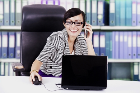 Happy asian businesswoman talking on the phone in the office photo