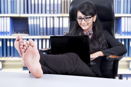 businesswoman legs: Successful Businesswoman using laptop with Feet Up on a Table, shot in the office