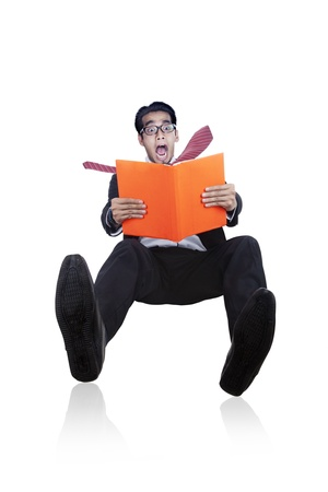 Careless businessman slipping and screaming when reading a book isolated on white photo