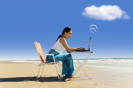 Cloud computing: working with laptop at beach photo