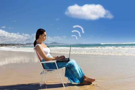 Cloud computing: Asian woman Working at the beach photo