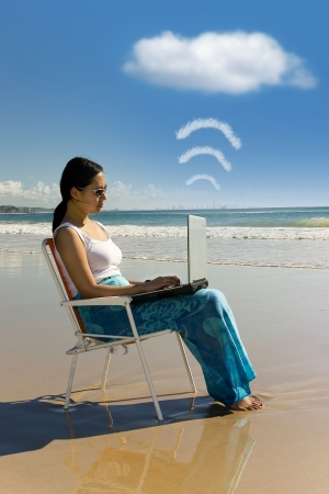 Cloud computing: woman with laptop working at the beach photo