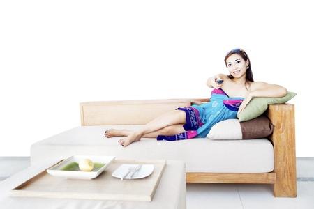 ver tv: Mujer joven que cambiar los canales de televisión con mando a distancia sentado en el sofá en casa